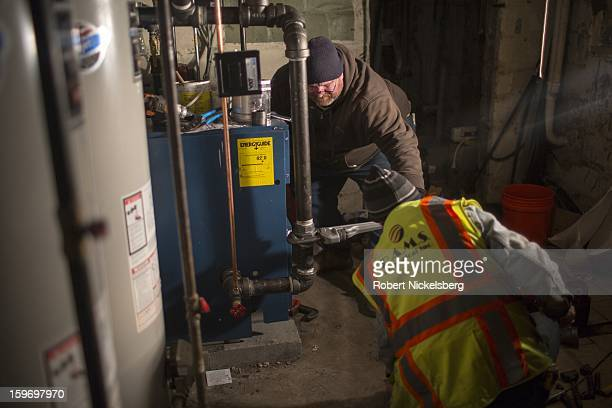 Plumbers install a new boiler in a basement at a private residence January 17 2013 flooded during Hurricane Sandy in the Rockaways January 17 2013 in...