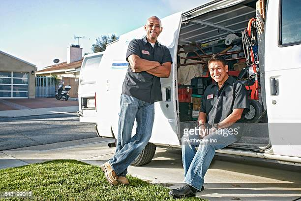 Plumbers smiling in van