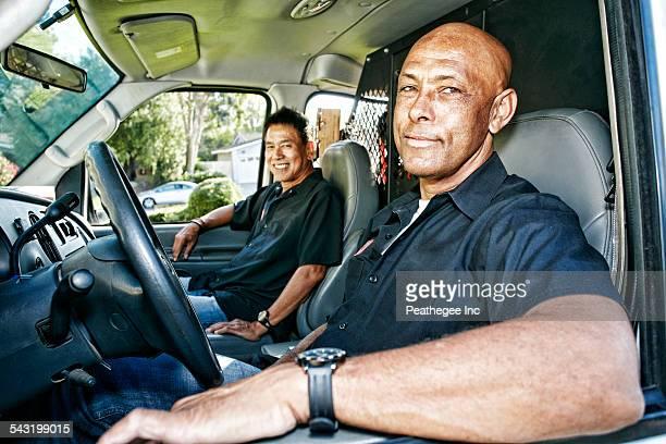 Plumbers smiling in van