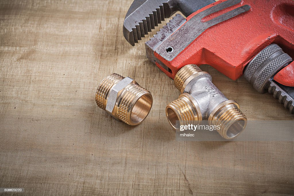 Plumbers wrench plumbing fixtures on mesh filter grid : Stock Photo