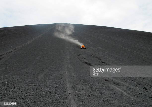 A plume of cinder and volcanic ash trail behind a man on a toboggan descending Cerro Negro It's called 'volcano boarding' and you'd better be brave...