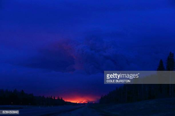 A plume of smoke hangs in the air as forest fires rage on in the distance in Fort McMurray Alberta on May 4 2016 Numerous vehicles can be seen...