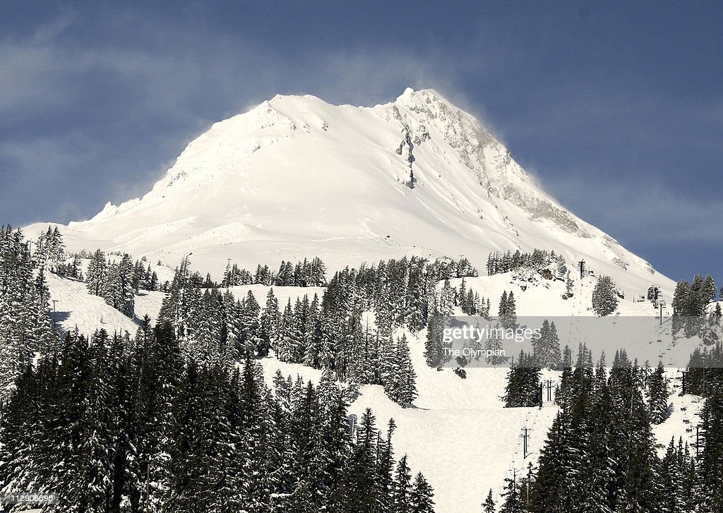 Plumes of wind-driven powder billow over Oregon's Mount Hood on a powder day at Mount Hood Meadows ski area.