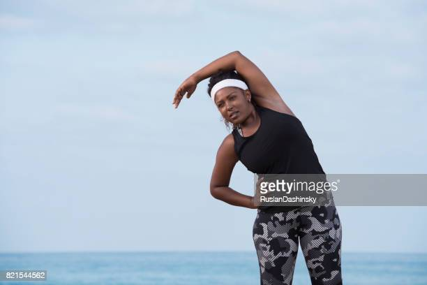 Plump woman doing stretching exercises outdoors. Aerobics fitness woman.