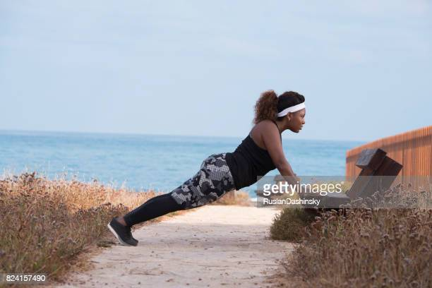 A plump woman on morning workout outdoors. Incline press-up.