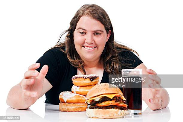 Plump young lady about to grab pile of junk food