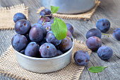 Plums in bowl on the wooden table