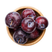 Plums in wooden bowl isolated on white background. Top view.