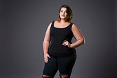 Plus size fashion model in casual clothes, fat woman on gray background, overweight female body, full length portrait