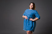 Plus size fashion model in casual jeans clothes, fat woman on gray background, overweight female body, studio shot