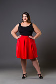 Plus size fashion model in red skirt, fat woman on gray background, overweight female body, full length portrait