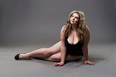 Young beautiful blonde plus size model in underwear, on gray studio background, full length portrait