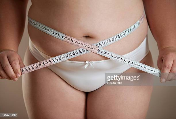 Plus size woman measuring her waste