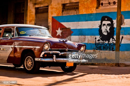 Plymouth classic car passing Cuban flag
