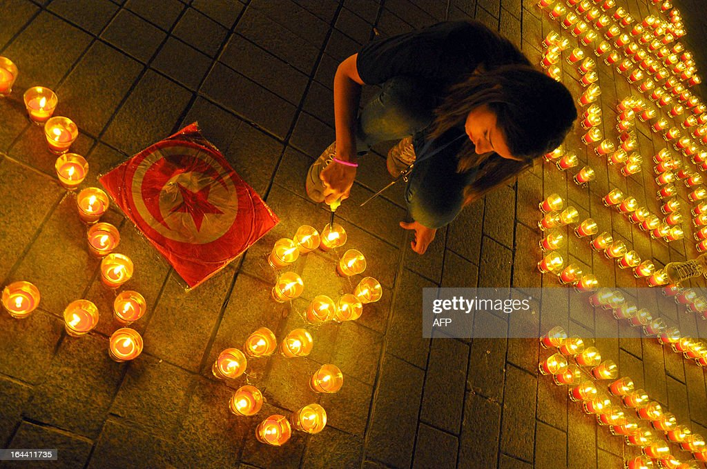This picture shows a woman lighting candles arranged to read 'Tunisia' in the Habib Bourguiba avenue after submerging into darkness as part of the Earth Hour switch-off in Tunis on March 23, 2013. Organisers expect hundreds of millions of people across more than 150 countries to turn off their lights for 60 minutes on Saturday night -- at 8:30 pm local time -- in a symbolic show of support for the planet. While more than 150 countries joined in last year's event, the movement has spread even further afield this year, with Palestine, Tunisia, Suriname and Rwanda among a host of newcomers pledging to take part.