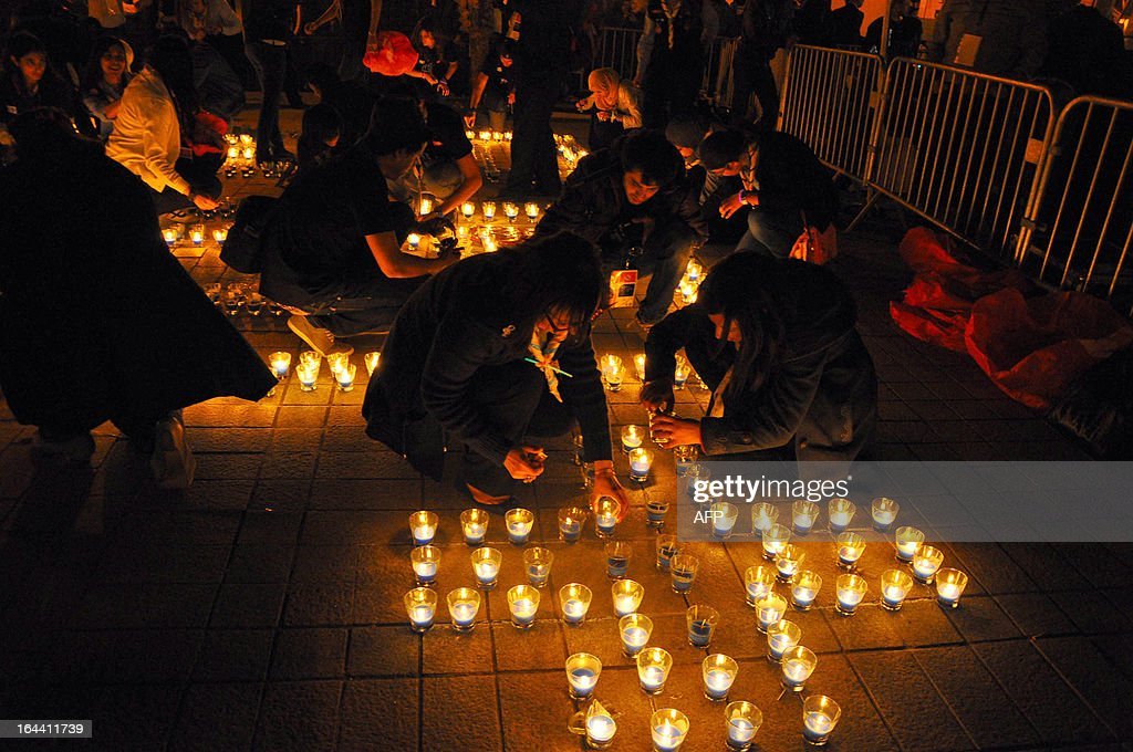 This picture shows people lighting candles arranged to read 'Tunisia' in the Habib Bourguiba avenue after submerging into darkness as part of the Earth Hour switch-off in Tunis on March 23, 2013. Organisers expect hundreds of millions of people across more than 150 countries to turn off their lights for 60 minutes on Saturday night -- at 8:30 pm local time -- in a symbolic show of support for the planet. While more than 150 countries joined in last year's event, the movement has spread even further afield this year, with Palestine, Tunisia, Suriname and Rwanda among a host of newcomers pledging to take part.