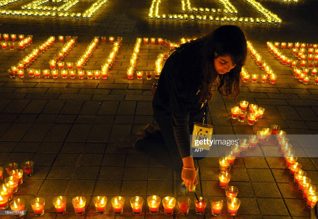 This picture shows a woman lighting candles arranged to read 'Tunisia' in the Habib Bourguiba avenue after submerging into darkness as part of the Earth Hour switch-off in Tunis on March 23, 2013. Organisers expect hundreds of millions of people across more than 150 countries to turn off their lights for 60 minutes on Saturday night -- at 8:30 pm local time -- in a symbolic show of support for the planet. While more than 150 countries joined in last year's event, the movement has spread even further afield this year, with Palestine, Tunisia, Suriname and Rwanda among a host of newcomers pledging to take part. AFP PHOTO / SAFA LAAMIRI