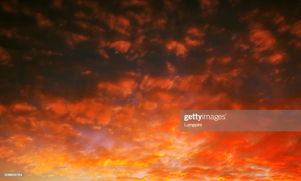 pocked fiery sky at sunset with sun rays : Stock Photo
