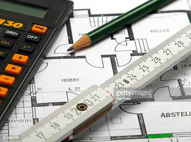 Pocket calculator, pencil and folding rule lying on a plan, construction of a house, planning