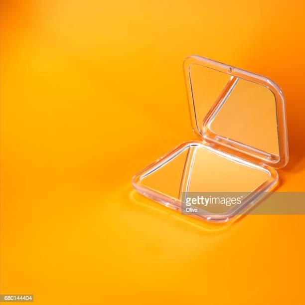 pocket mirror on orange background