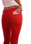 A deeply tanned woman grasps currency in her back pocket.  She is wearing red jeans and a white top.