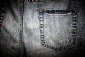 Close-up of a plain back pocket of a pair of well-worn and tattered jeans.