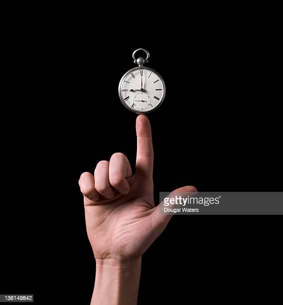 Pocket watch balanced on tip of finger.