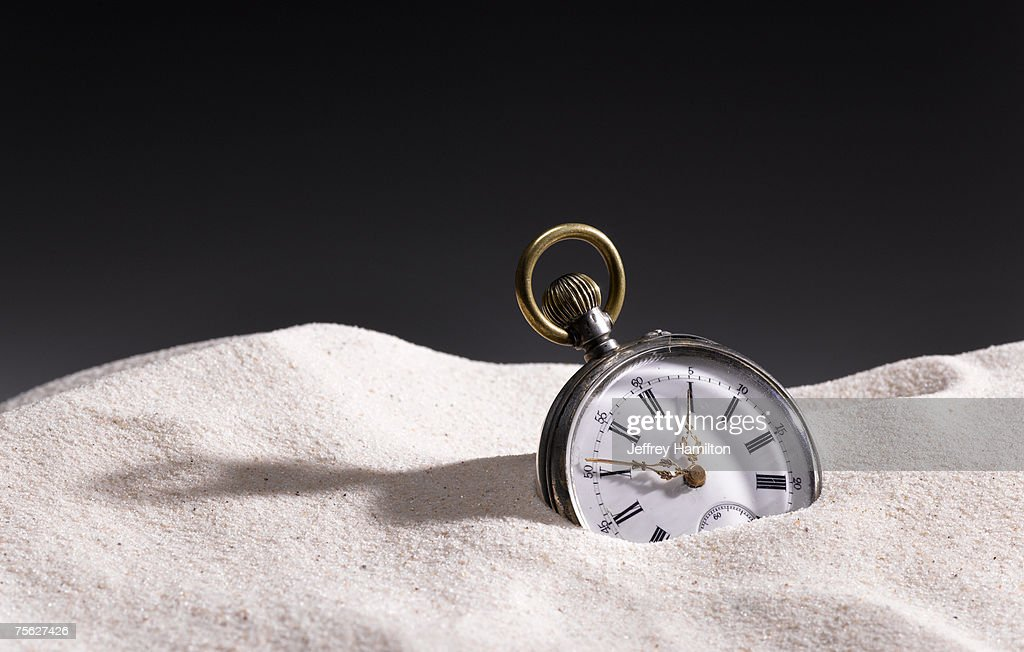 Pocket watch in sand : Stock Photo