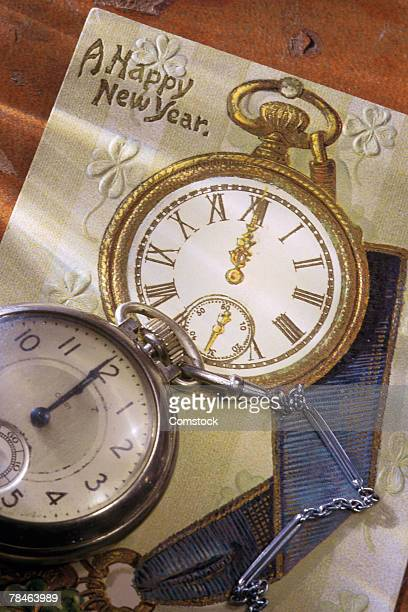 Pocket watch on top of New Year's greeting card