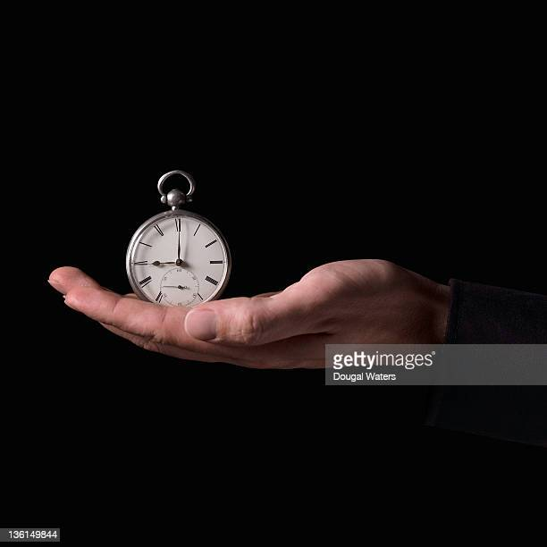 Pocket watch resting in palm of hand.