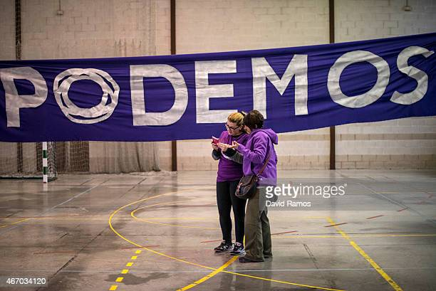 Podemos supporters check pictures in their camera in front of a huge banner before a political campaign rally on March 19 2015 in Cadiz Spain Podemos...