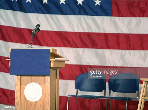 Podium with USA flag backdrop and chairs by it
