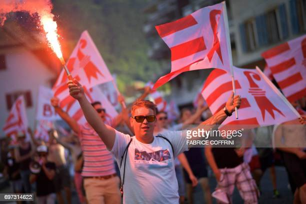 Poeple celebrate with flares after the commune of Moutier voted to join primarily Frenchspeaking canton Jura on the election day concerning the...