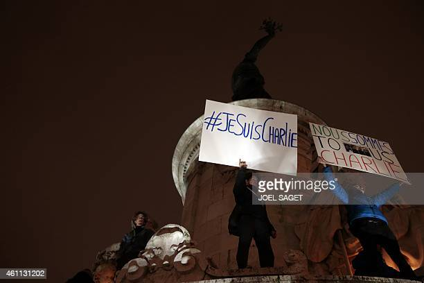Poeple hold placards reading in French 'I am Charlie' and 'We are all Charlie' during a gathering at the Place de la Republique in Paris on January 7...