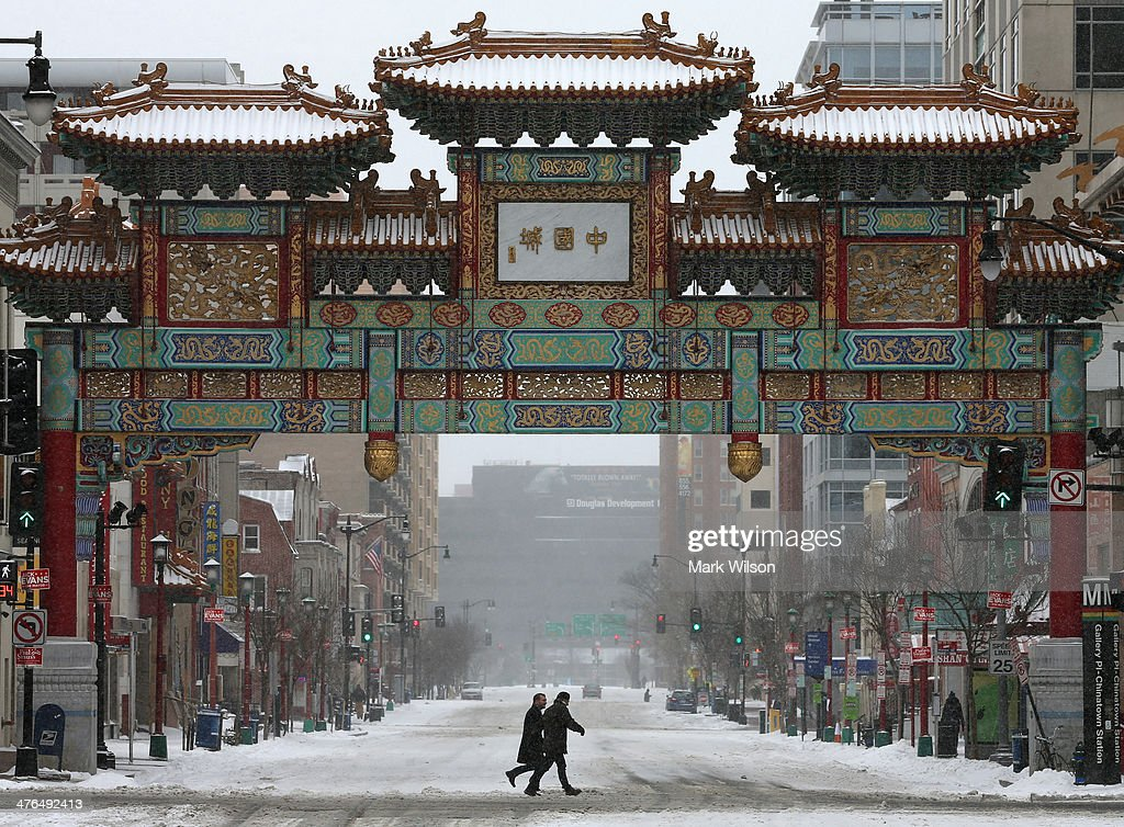 Poeple walk in the snow near the China Town arch on March 3, 2014 in Washington, DC. The Federal Governent is closed due to major snow storm that is expected to dump up to 8' of snow in the Washington area.