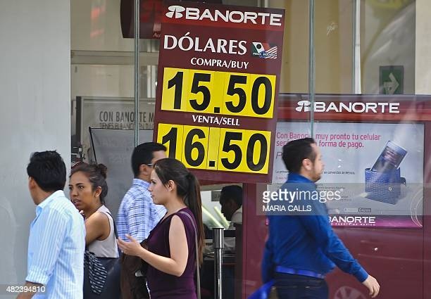 Poeple walk outside a bank displaying the exchange rate between the dollar and the Mexican peso in Mexico City on July 30 2015 The Bank of Mexico...