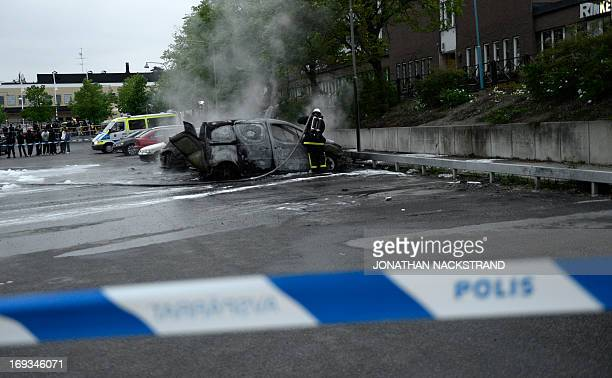 Poeple watch as a fireman extinguishes a burning car in the Stockholm suburb of Rinkeby after youths rioted in several different suburbs around...