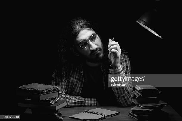 Poet writing on table in the dark