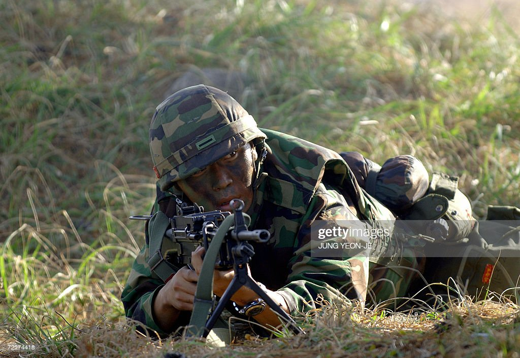 A South Korean marine takes position after a landing during a military drill in Pohang, some 374 Km southeast of Seoul, 27 October 2006. South Korea staged a military landing exercise amid the heightened tension over North Korea's nuclear test. AFP PHOTO/JUNG YEON-JE