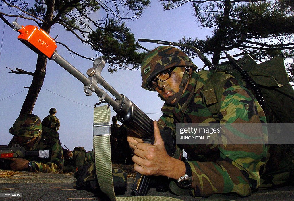 South Korean marine take position after a landing during a military drill in Pohang, some 374 Km southeast of Seoul, 27 October 2006. South Korea staged a military landing exercise amid the heightened tension over North Korea's nuclear test. AFP PHOTO/JUNG YEON-JE