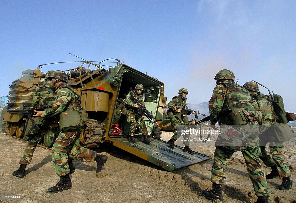South Korean marines prepare to take position after a landing during a military drill in Pohang, some 374 Km southeast of Seoul, 27 October 2006. South Korea staged a military landing exercise amid the heightened tension over North Korea's nuclear test. AFP PHOTO/JUNG YEON-JE