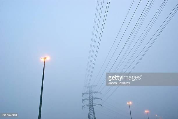 Electricity tower, power cables and freeway lights on a foggy morning.