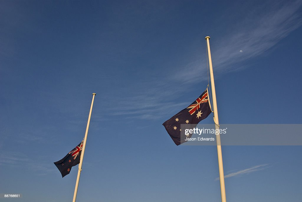 Dawn on ANZAC Day and Australian and New Zealand flags at half mast.