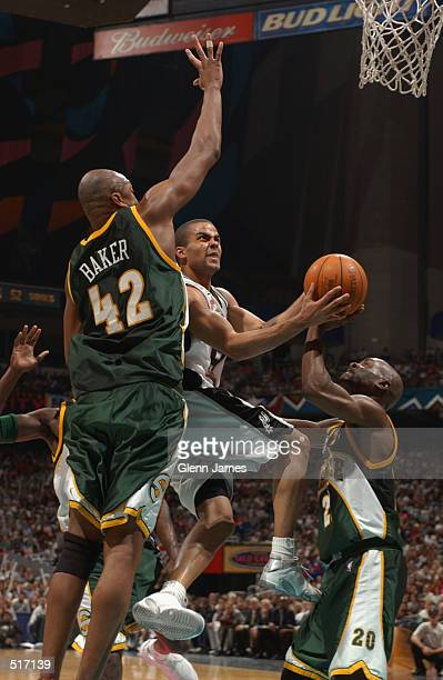 Point guard Tony Parker of the San Antonio Spurs shoots past forward Vin Baker and point guard Gary Payton of the Seattle SuperSonics during game...