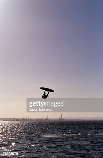 The silhouette of a person kite surfing, in a choppy windswept bay. : Stock Photo