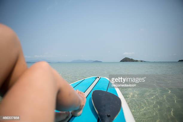 Point of view from woman's perspective sitting on paddle board-Tropical