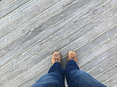 Point of view (POV) looking down at feet, standing on a wooden boardwalk at Coney Island, Brooklyn, New York.  Looking down at brown shoes wearing denim jeans, outside on a wooden pier.