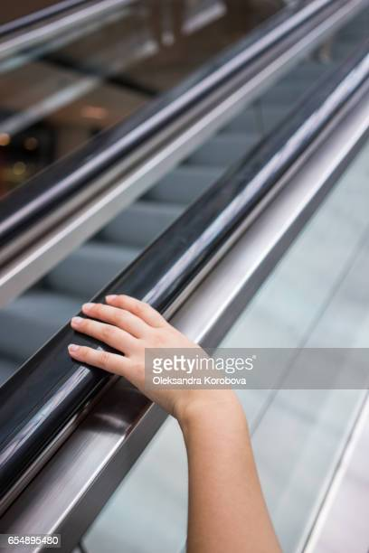 Point of view of a female riding an escalator to the second floor of the mall.