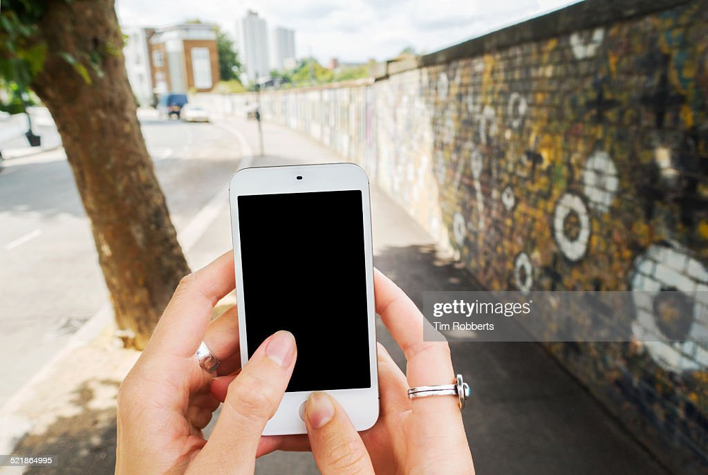 Point of view shot of mobile phone, graffiti wall.