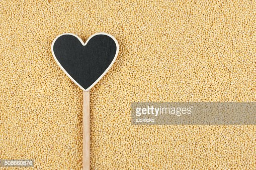 Pointer in the form of heart lies on millet grains : Stock Photo